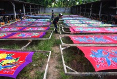 Three men stretch lengths of dyed sarong on wooden frames to dry and shape them under the sun. JP/Aman Rochman