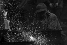 A worker uses a welding tool to cut the metal of a ship. JP/Sigit Pamungkas