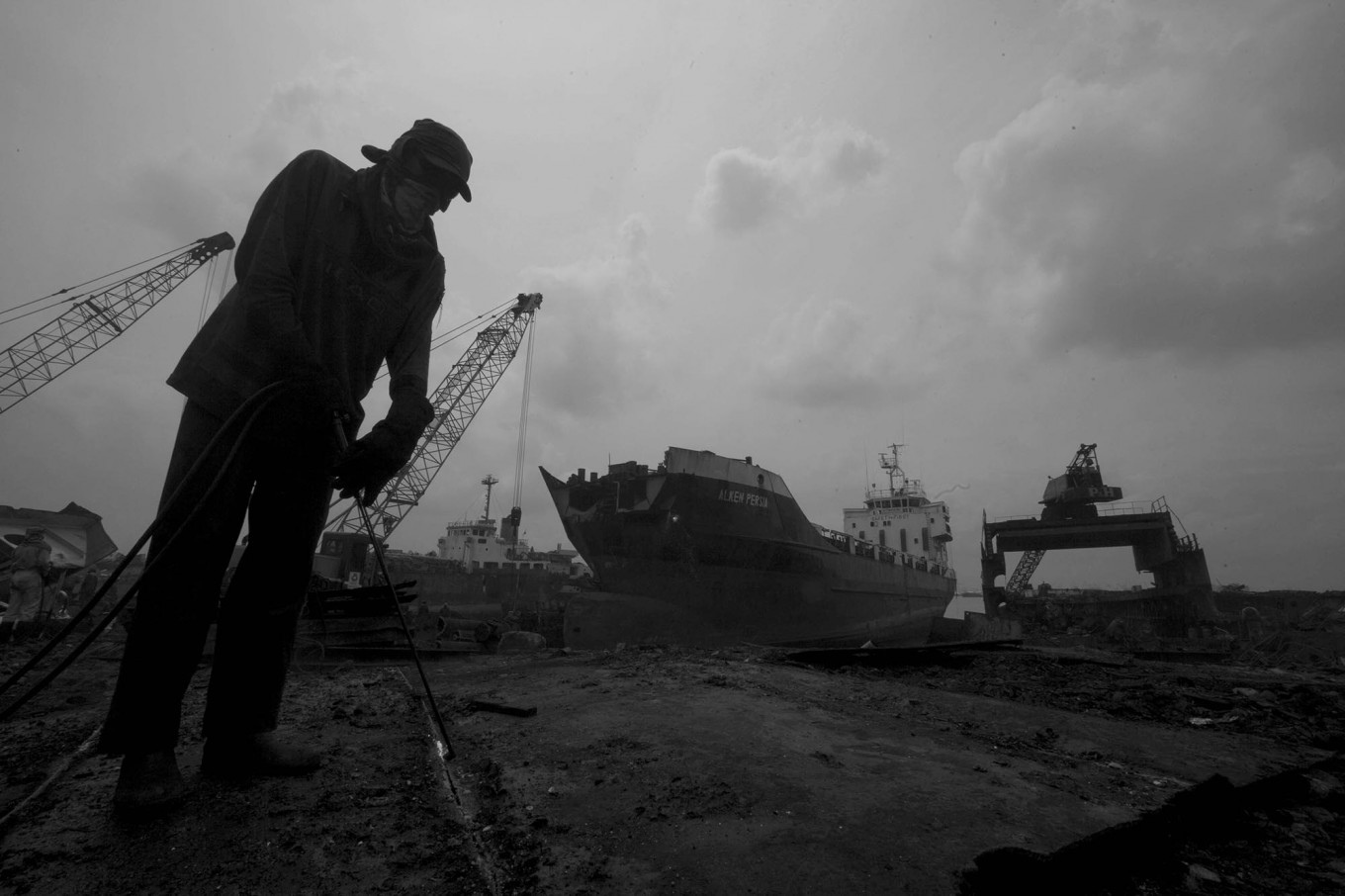 A worker cutting metal on a dock in Kamal, Madura Island, East Java, on Monday, Jan. 23, 2017. The sheet metal is sold to a smelter. Each worker earns Rp 100,000 per day. JP/Sigit Pamungkas