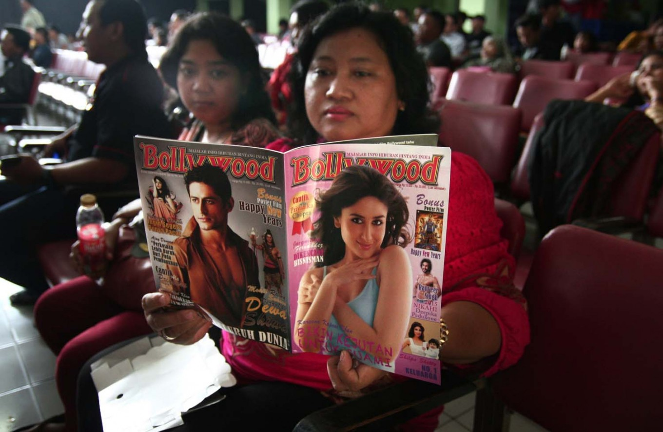 A visitor reads a Bollywood magazine while waiting for the Bollywood festival to start at the Gajayana Playhouse in Malang, East Java, on Sept. 21, 2014. JP/Aman Rochman