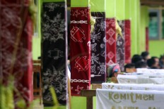 Batik with various motifs, mostly modern ones such as android symbols, created by new students hangs on the wall during the student orientation program. JP/Aditya Sagita