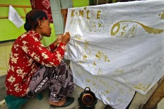 A new student signs an integrity pact using a canting (a pen-like tool used in making batik). The pact said they would not become involved in violent acts and drugs. JP/Aditya Sagita