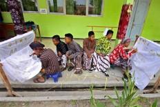 Two male students create batik while their classmates look on. JP/Aditya Sagita
