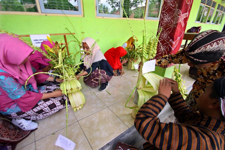Students create wedding ornaments made of janur (young coconut leaves). JP/Aditya Sagita