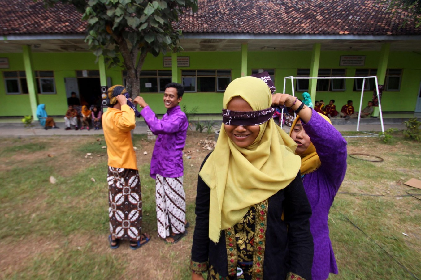 Two new students help classmates put on blindfolds during the masangin competition in which participants run between two trees. JP/Aditya Sagita