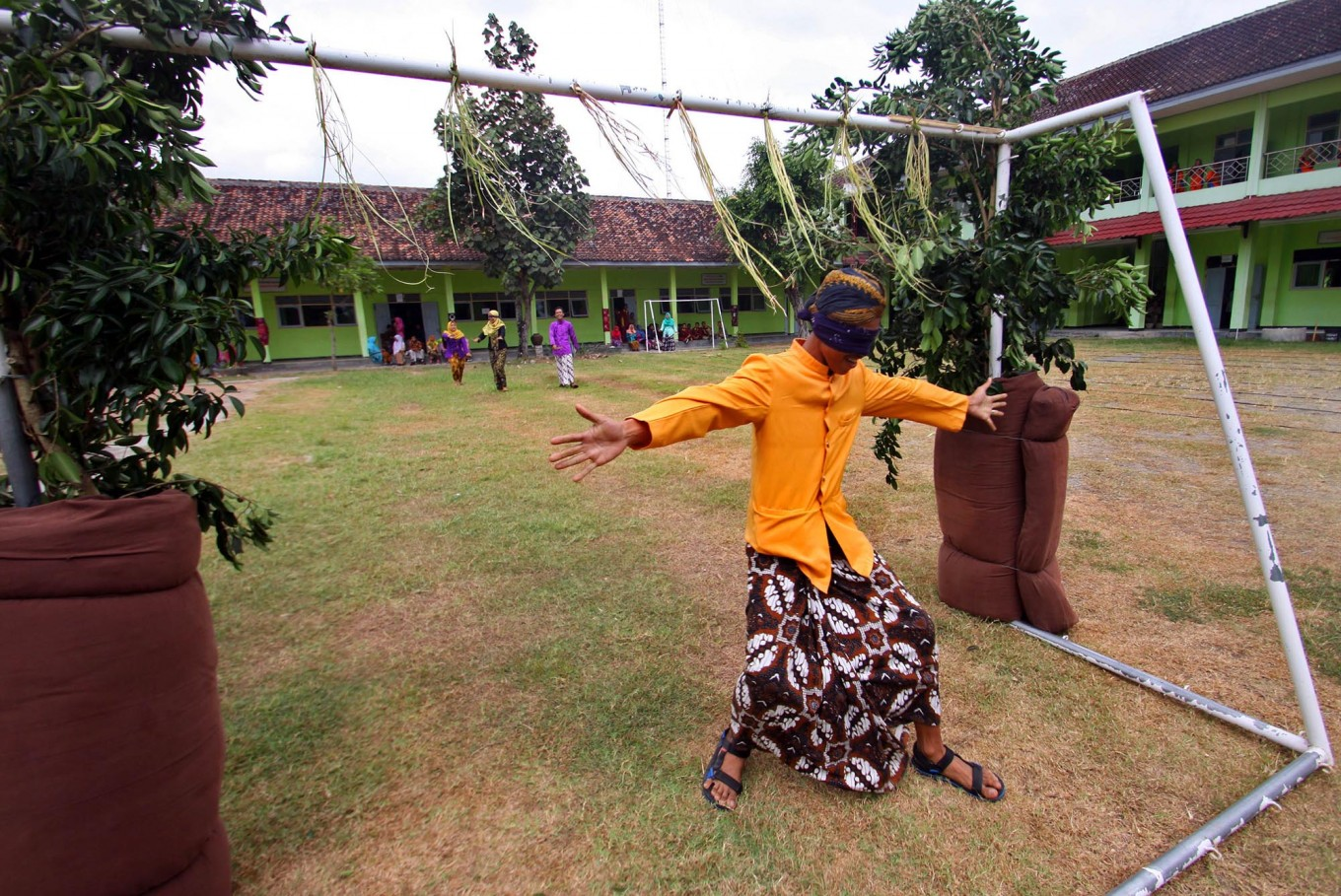 A male student gestures after passing between two trees in the masangin competition in the school orientation program. JP/Aditya Sagita