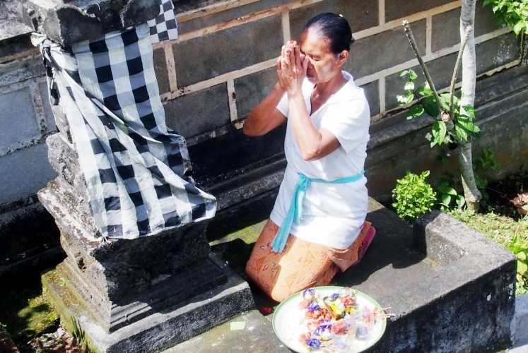Respecting the gods: A resident places offerings and prays in front of a monument by her house.
