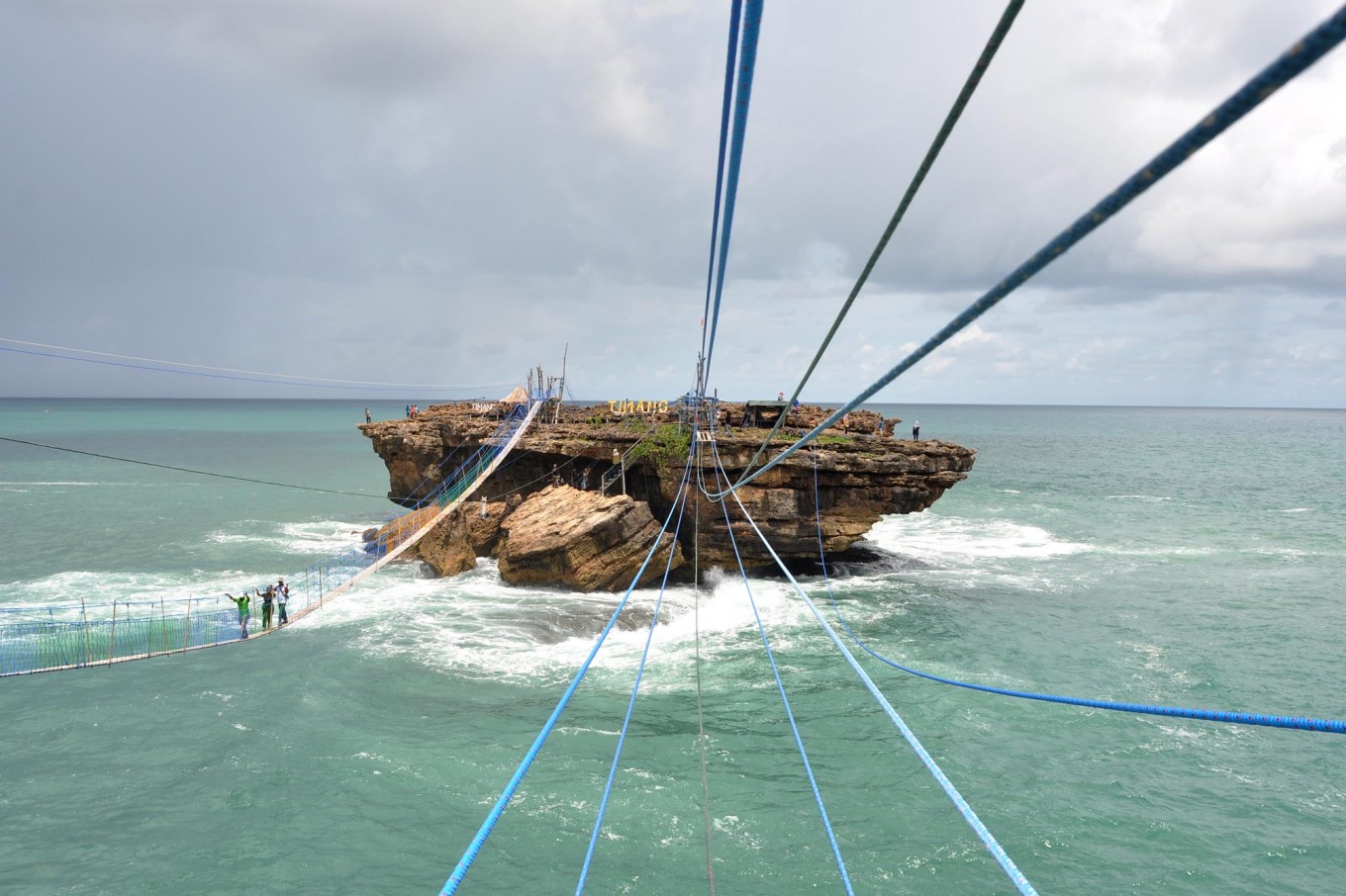 Some tourists prefer to cross the strait to Timang islet by using a hanging bridge. The bridge is made of 500 wooden planks lined up along 100 meters. JP/Magnus Hendratmo