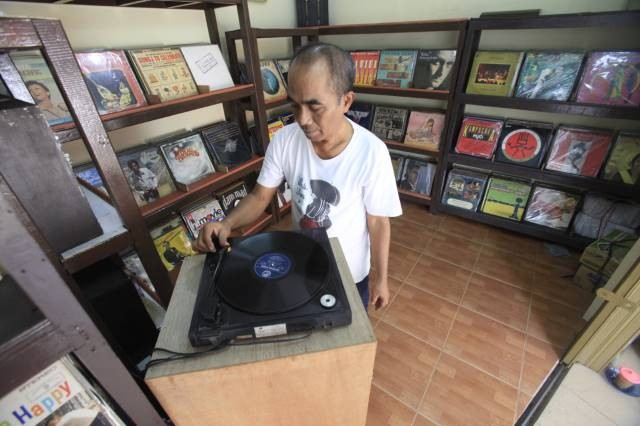 Old guard: Owner of Lian Store, Lian Nasutian plays an old Indonesian record for customers inside his roadside music shop on Jl. Surabaya, Menteng, Central Jakarta.