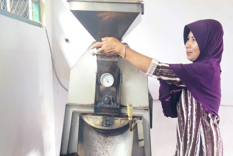 Work in progress: A woman processes Arabica coffee beans at the Selencak Mini Farm in Sumber Wringin, Bondowoso.