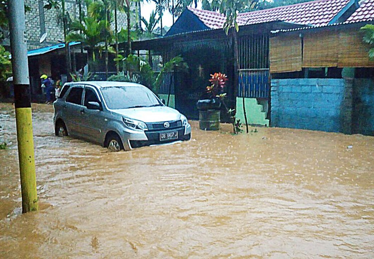 A car is stuck in floodwater at the Organda residential complex in Padangbulan, Jayapura, Papua, on Thursday. Jayapura is one of the cities to get the Adipura Award from the Forestry and Environment Ministry this year. The award is given to cities and regencies for achievements in cleanliness, healthiness and sustainable development.