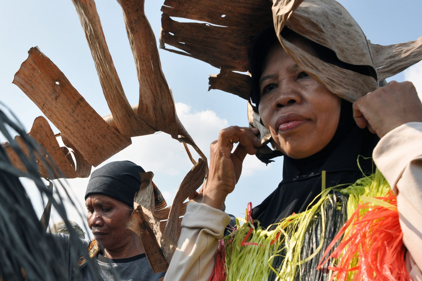 Two women get ready to perform Gejog Lesung by placing dried banana leaves on their heads. JP/Magnus Hendratmo