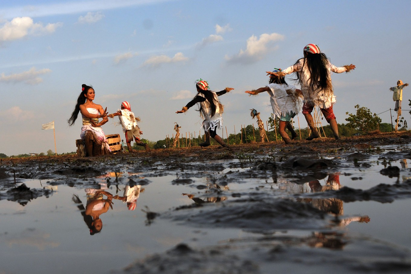 """Lintang, a professional dancer, adopts her role as Ibu Pertiwi during the Mbok Sri Mulih performance while other dancers take roles as """"memedi sawah"""" (scarecrows), a symbol of pest expulsion. JP/Magnus Hendratmo"""