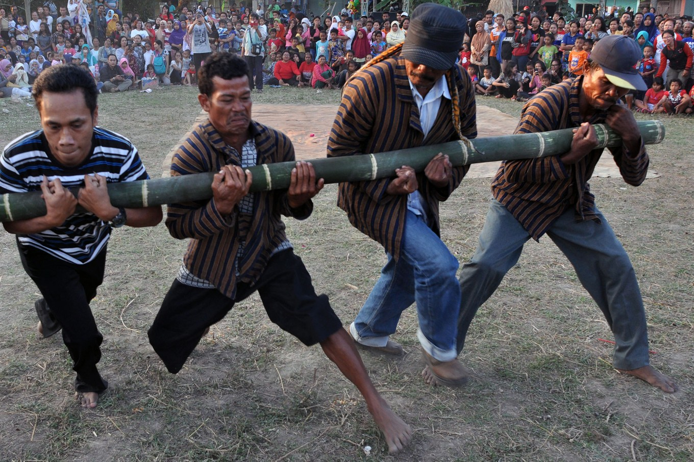Four men play Bambu Gila (crazy bamboo), a mystical ritual usually performed on Indonesia's Maluku Islands, where a group of strong men struggle to control a piece of bamboo, which moves uncontrollably as if it were possessed by a supernatural power. JP/Magnus Hendratmo