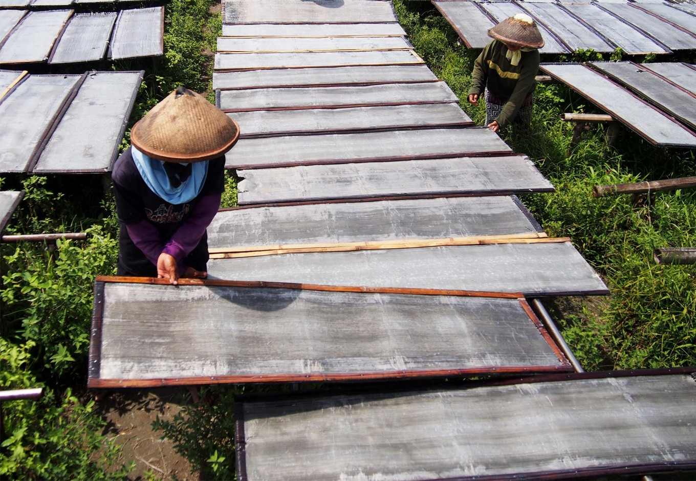 Two workers arrange trays of vermicelli to be dried in the sun. JP/Ganug Nugroho Adi