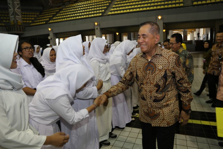 Defense Minister Ryamizard Ryacudu shakes hands with new students at the University of Indonesia at the university's campus in Depok, West Java, on Friday.