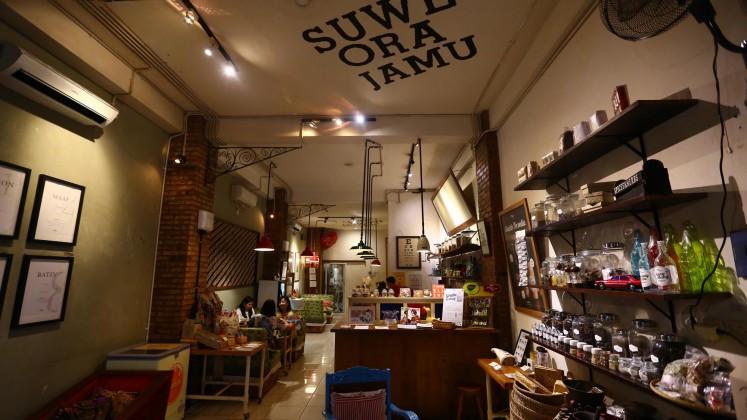 Customers enjoy food and jamu (herbal drinks) at Suwe Ora Jamu cafe.