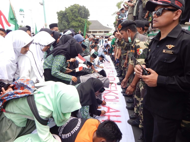 Thousands of Nahdlatul Ulama members and Islamic school students sign a large white banner during a rally at Purwokerto town square in Banyumas, Central Java, on Monday. They demanded the annulment of the controversial five-day school policy issued by Culture and Education Minister Muhadjir Effendy.