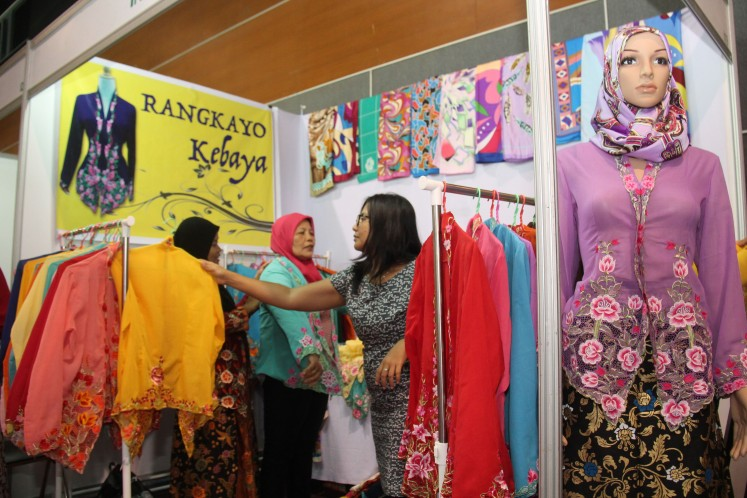 Visitors look through products displayed at the Rangkayo Kebaya booth from Payakumbuh, West Sumatra, during the 2017 World Halal Products Expo at the International Conference Center in Hat Yai, Thailand, on July 13-16, 2017.