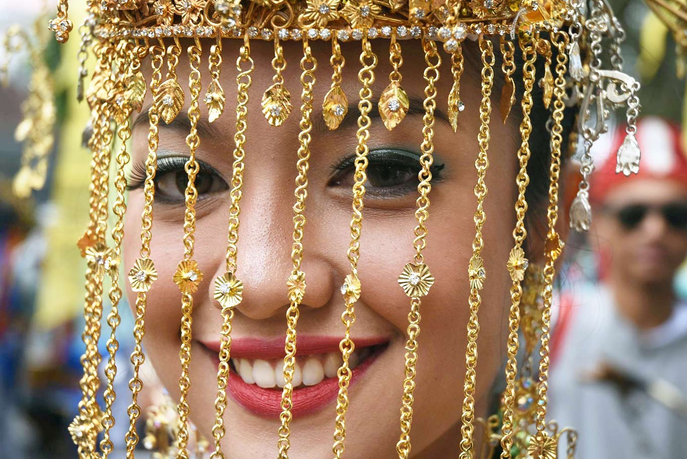 Veiled beauty: A participant from Tangerang, Banten, smiles behind the beautiful beaded veil of a traditional wedding costume.