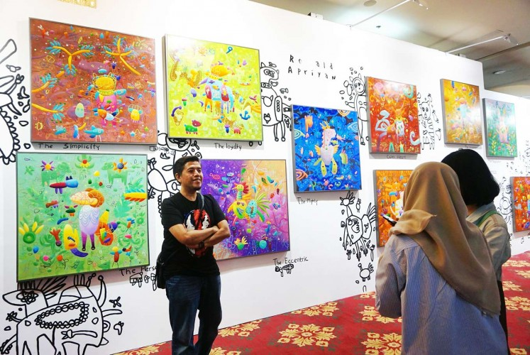 Youthful force: A visitor poses with Ronald Apriyam's paintings at Art Jakarta 2017 at Pacific Place in Jakarta. The arts fair, previously known as Bazaar Art, showcased a wide range of works by young artists and positioned itself as the people's arts fair.