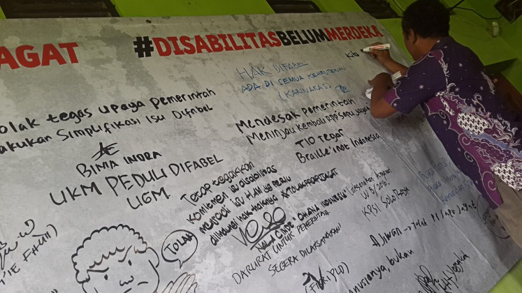 Independent voice: A man expresses his opposition to the government's plan to issue only one government regulation to implement Law No. 8/2016 on People with Disabilities on a large banner at an Aug.10 advocacy event in Yogyakarta.