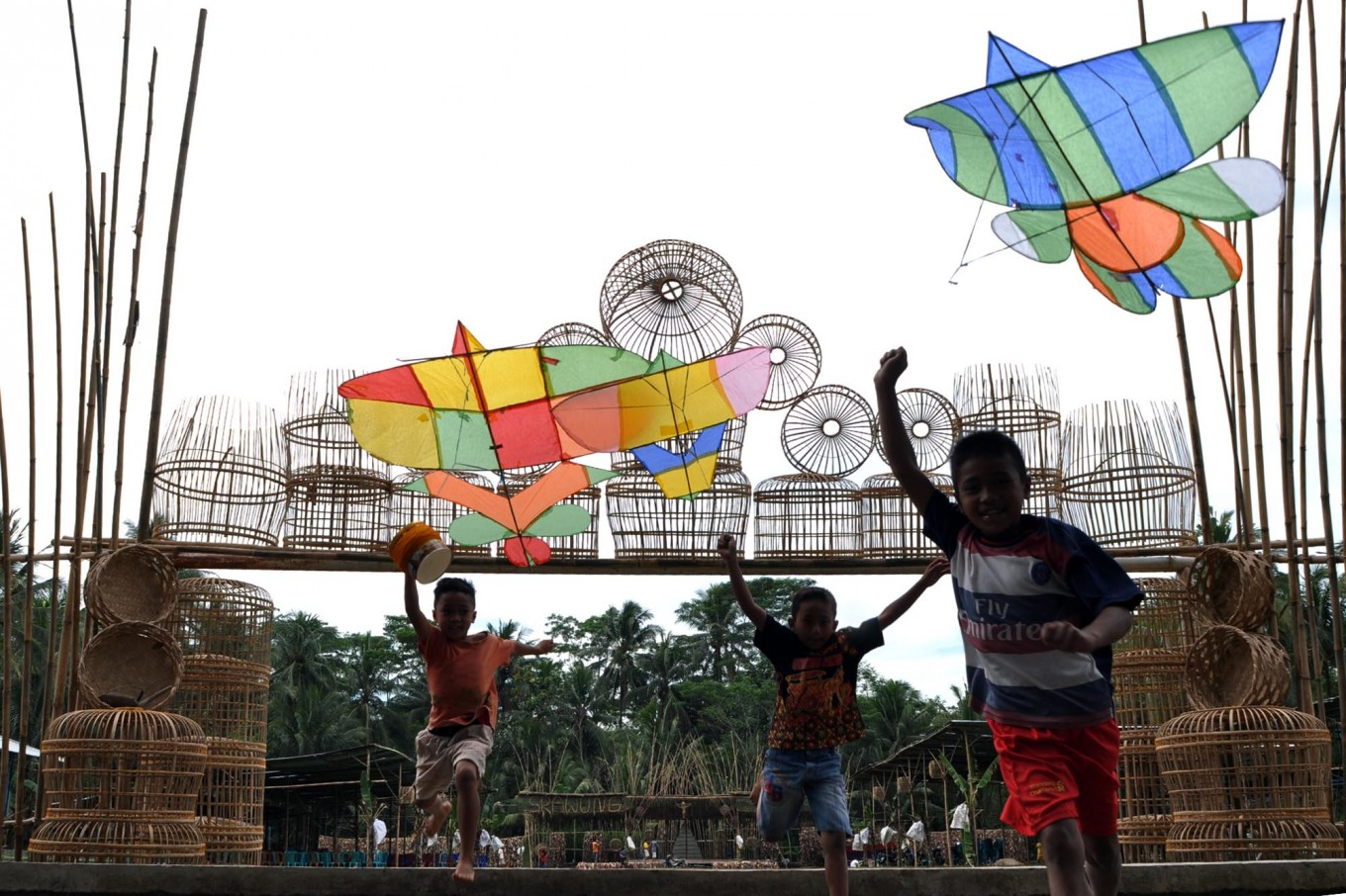 Three boys run to fly a kite at Bunder village. The kites are made of bamboo with creative shapes and colors. People of Bunder mostly work as a bamboo weavers producing cages. JP/ Magnus Hendratmo