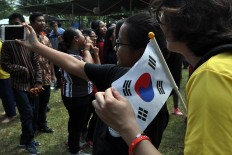 A Korean participant in the 2017 Asian Youth Day, holding her country's flag, has her photo taken during the Srawung Asih performance. JP/ Magnus Hendratmo