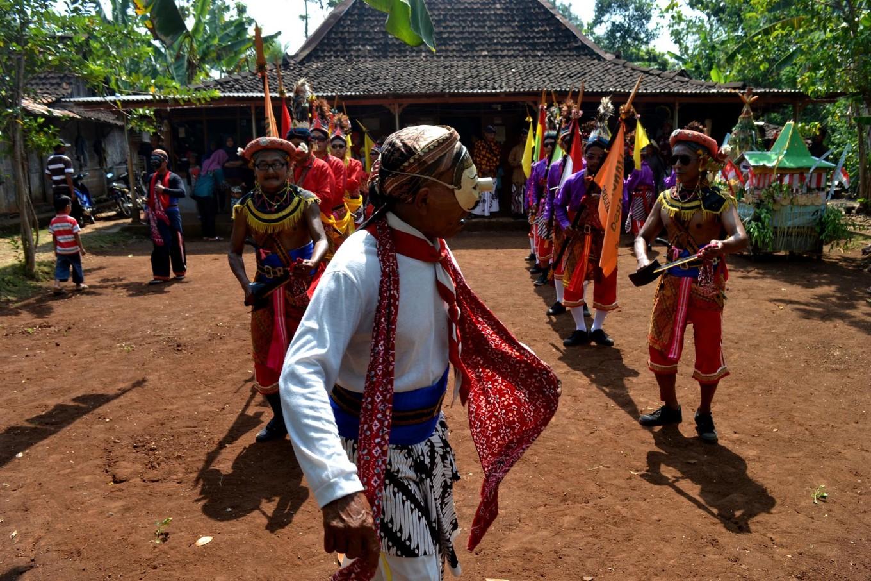 A man wearing a mask dances in front of a Bejiharjo village leader to collect cone offerings. JP/Stefanus Ajie