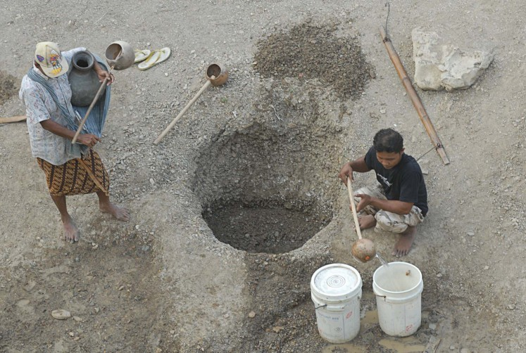 Musuk residents in Boyolali, Central Java, take water from an excavated well in a dried-up river recently.