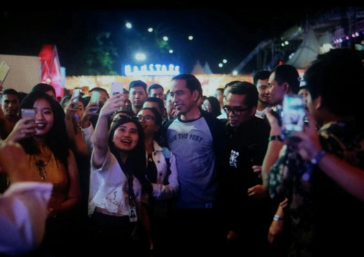 Excited festival-goers take selfies with the President.