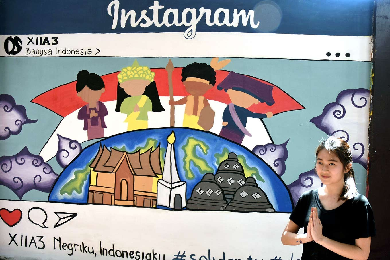 Socmed savvy: Valerie, a senior, poses in front a mural, which depicts an Instagram screen interface.