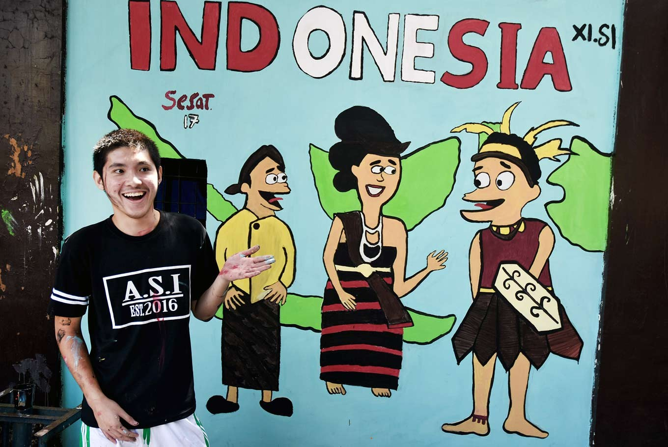 Coast to coast: Keneth, an 11th grader, poses in front of a mural, which depicts the three main parts of the Indonesian archipelago - the western, central and eastern.
