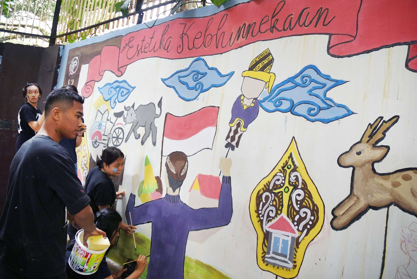 United in diversity: Students of the Santo Albertus Catholic senior high school in Malang, East Java, paint a mural on the wall of their school.