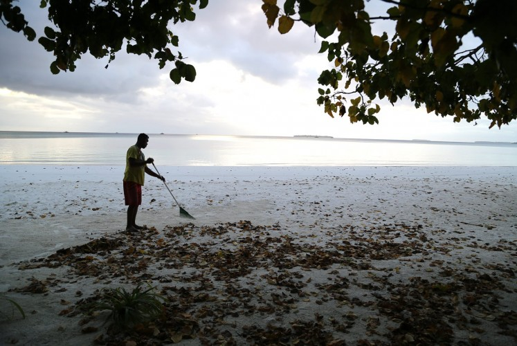 Ngurbloat beach: A resident sweeps up leaves at Ngurbloat beach, the name of which means