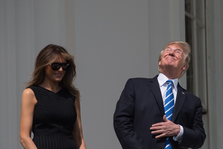 US President Donald Trump and First Lady Melania Trump look up at the partial solar eclipse from the balcony of the White House in Washington, DC, on August 21, 2017. The Great American Eclipse completed its journey across the United States Monday, with the path of totality stretching coast-to-coast for the first time in nearly a century. Totality began over Oregon at about 1716 GMT and ended at 1848 GMT over Charleston, South Carolina where sky-gazers whooped and cheered as the Moon moved directly in front of the Sun.