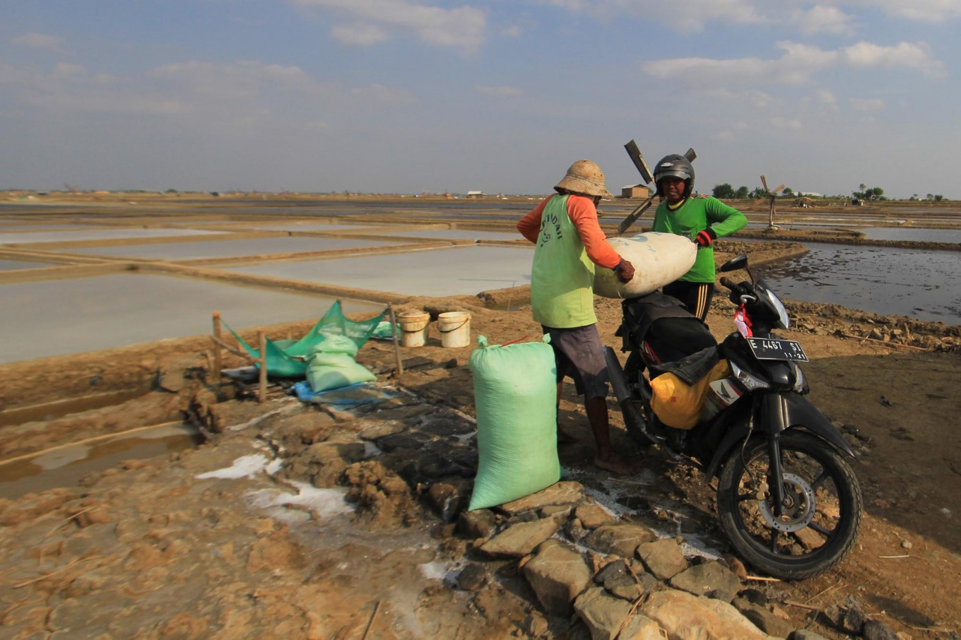 Two farmers lift sacks of salt into a motorcycle. They will sell the salt to a collector in Santing village. Antara/Dedhez Anggara
