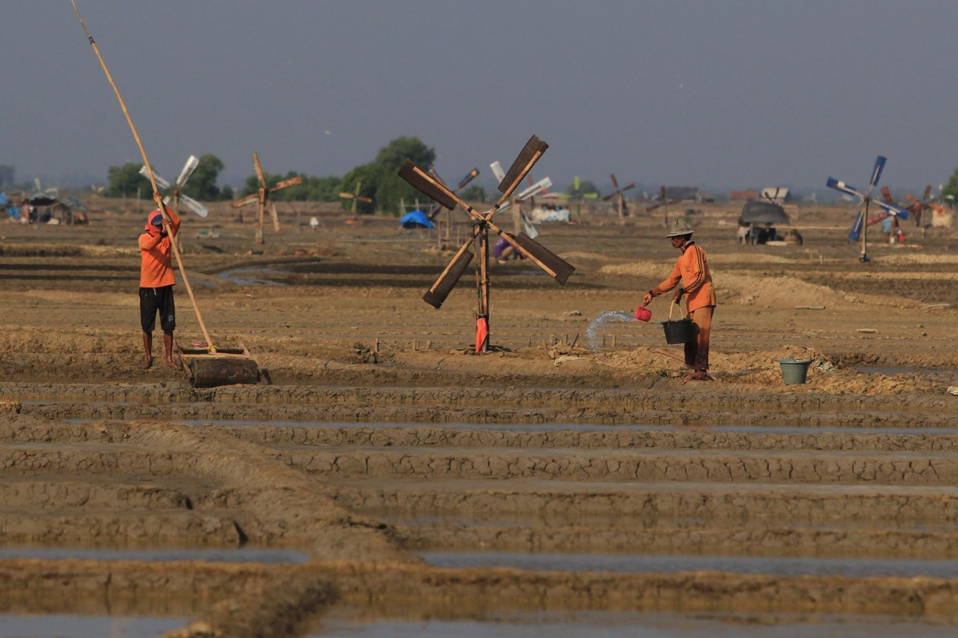 Two farmers cultivate their salt fields in Santing village. Antara/Dedhez Anggara