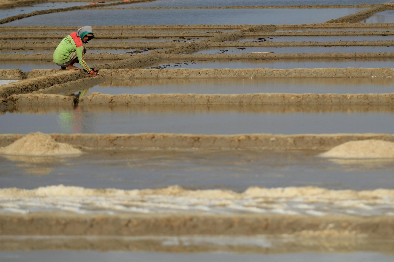A farmer checks the water on his salt field. Antara/Dedhez Anggara