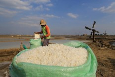 A farmer fills up a sack of salt. Antara/Dedhez Anggara