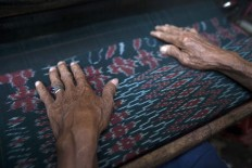 Quality control: each Parengan fabrics needs to undergo tight quality control. Crafts-men use their bare hands to feel and sense the details and quality of the fabric. JP/ Sigit Pamungkas