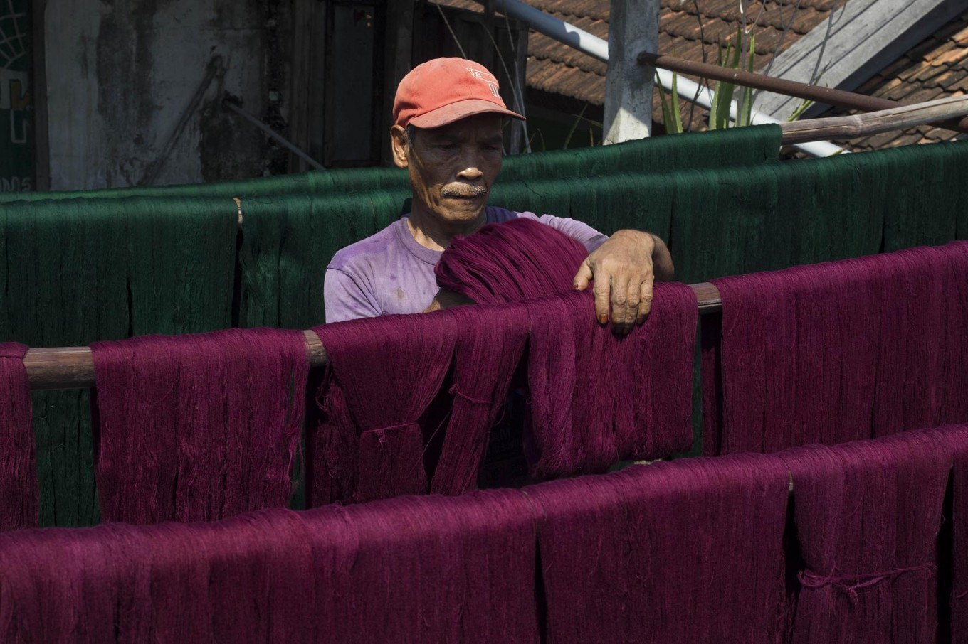 Processing: A man puts threads that have been colorized under the sun so that they can last longer. JP/ Sigit Pamungkas