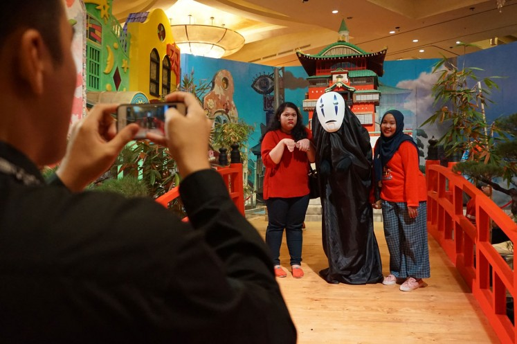 Two female visitors take pictures with Kaonashi with the help of one of the exhibition's attendants at The World of Ghibli Jakarta exhibition.