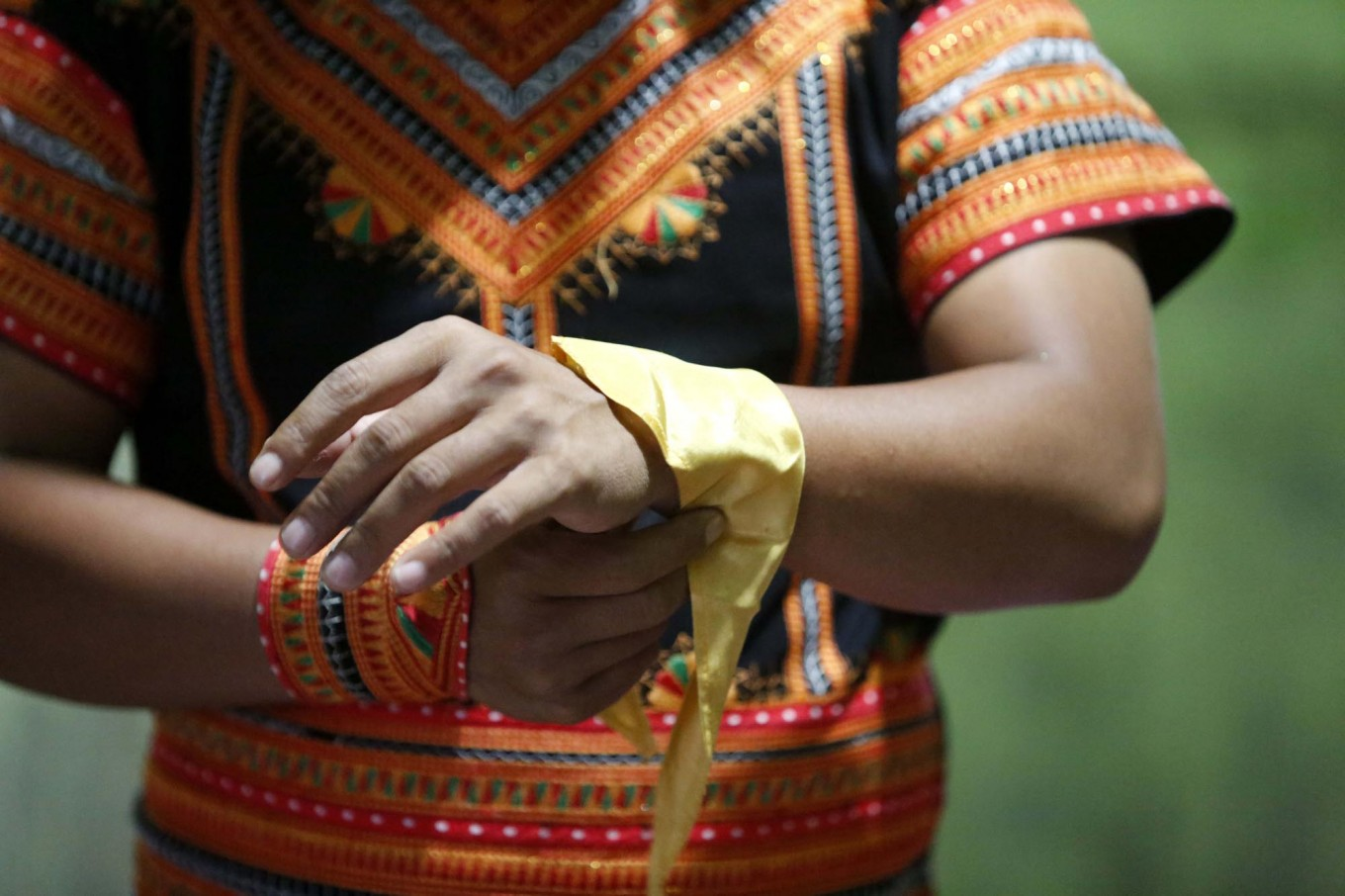 Alimudin ties a yellow handkerchief on his left wrist before performing in the mass dance. JP/Hotli Simanjuntak