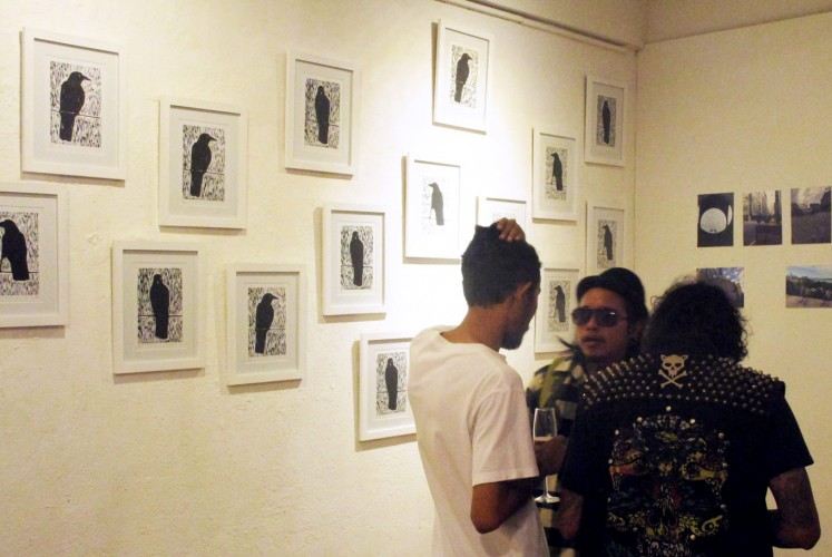 Visitors converse in front of the 'Black Bird' series of linocut on paper.