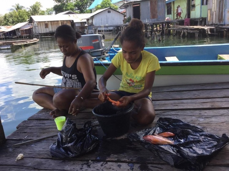 Struggle for life: Local women from Hobong village, Sentani, Papua, go fishing. Hobong villagers depend on Sentani Lake for their livelihood.