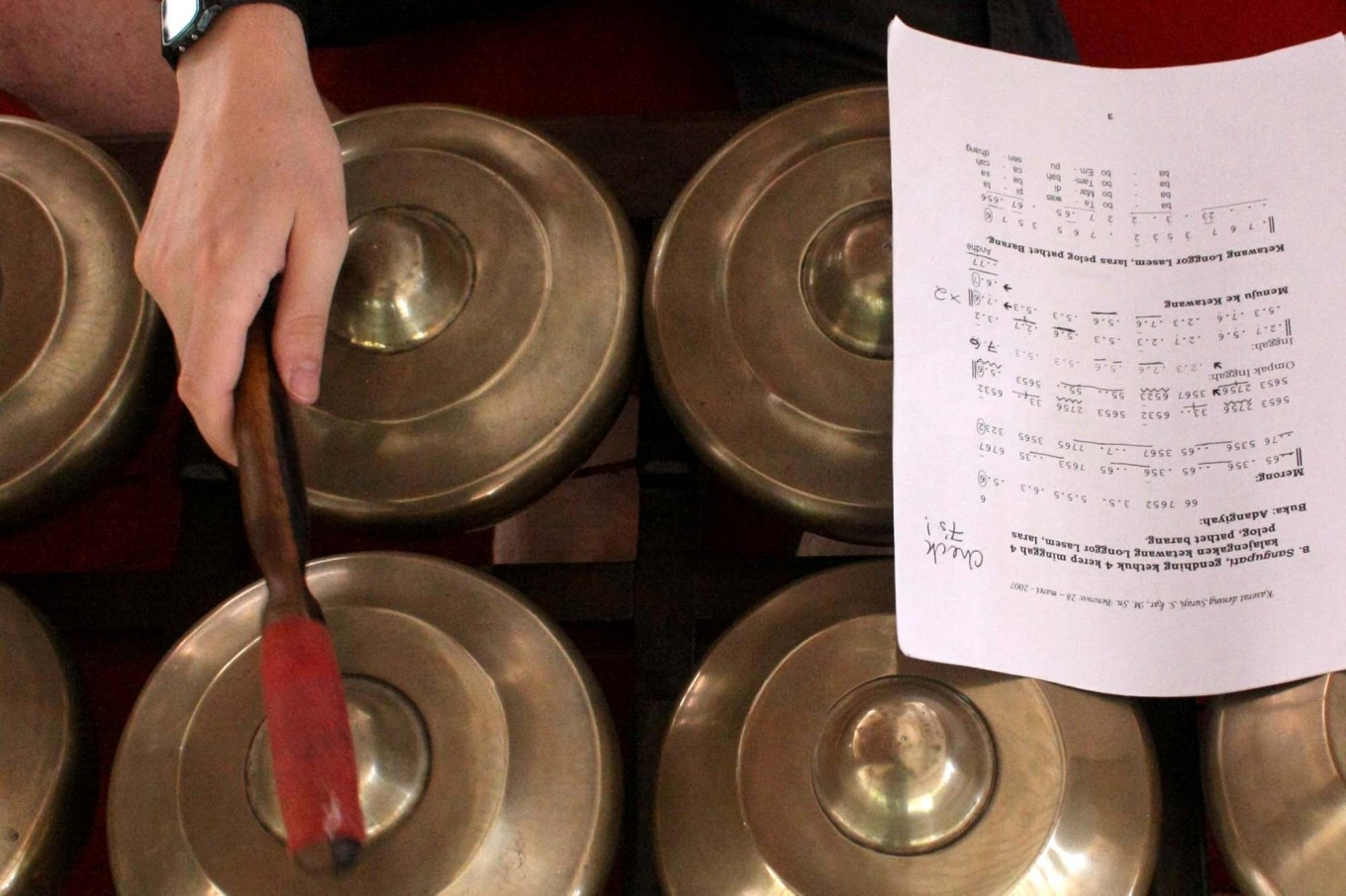 A gamelan instrument is played while a note is laid on top of it during rehearsal. JP/Maksum Nur Fauzan
