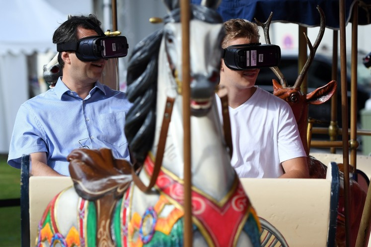 Visitors sitting on a carousel try out virtual glasses at the booth of Deutsche Telekom at the IFA Consumer Electronics Fair in Berlin on September 2, 2017.