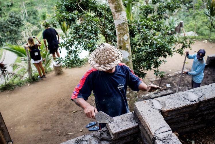 On progress: Wayan Arnawa (center) builds a simple kitchen around the paddy field tourist site in Ceking.