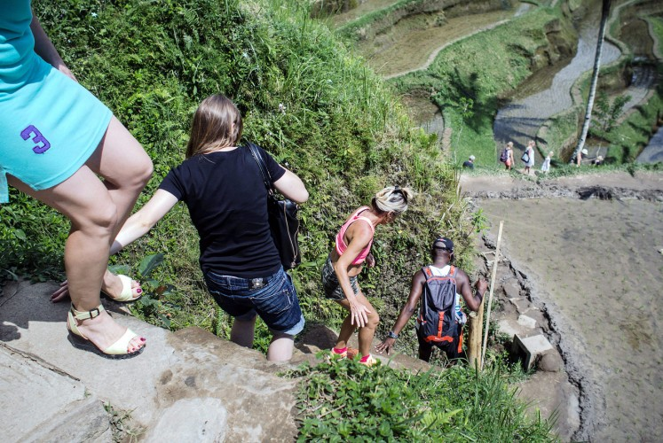 Step by step: Foreign tourists climb down the paddy terrace wall in Ceking.